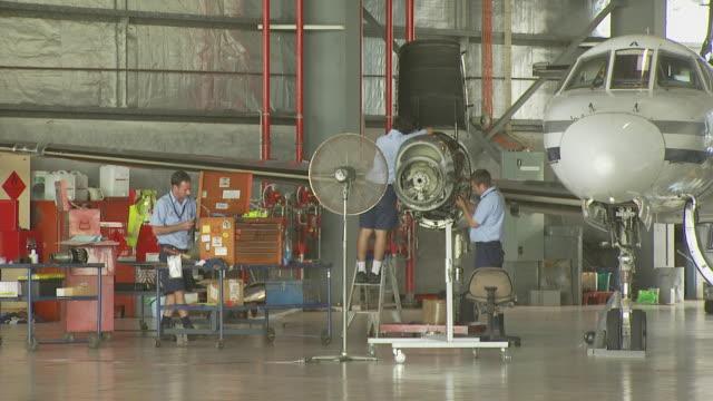 Engineers in hangar performing maintenance on Metroliner engine, Australia