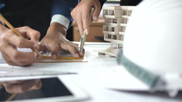 Engineers-teamet som arbetar på en ritningsplan