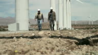 Engineers walking through wind farm