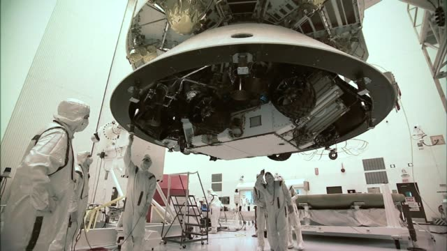/ NASA engineers wearing protective white clothing prepare Mars Curiosity Rover for launch on Atlas V rocket Engineers prepare Mars Curiosity Rover...