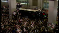 England bring home the Webb Ellis Cup after winning the 2003 Rugby World Cup Shows exterior shots fans surrounding the team bus as the coach can...