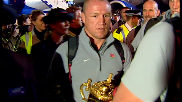 England bring home the Webb Ellis Cup after winning the 2003 Rugby World Cup Shows exterior shots Johnny Wilkinson with teammates Neil Back carrying...