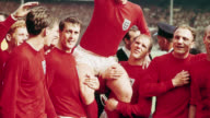 England football captain Bobby Moore lifts the Jules Rimet Trophy with his team after England's World Cup victory over West Germany.