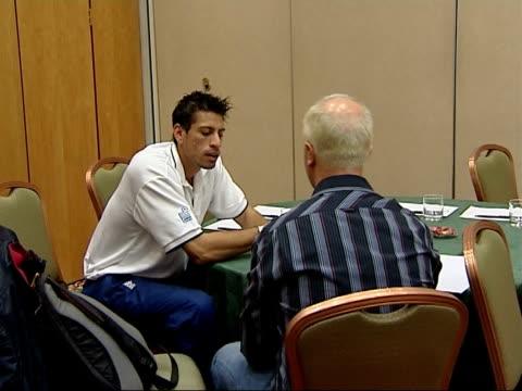 England team signing cricket bats Mahmood chatting to unidentified man