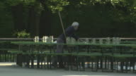 Englischer Garten - Chinesischer Turm, Biergarten, man cleans up, empty benches and tables, many jars