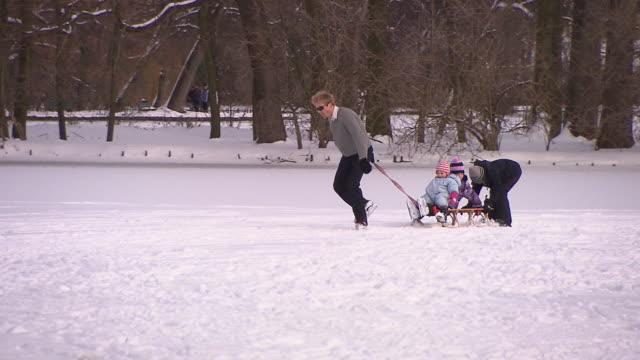 Englischer Garten, man on ice skates pull a sledge with his children, winter, snow