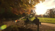 Englischer Garten, people sitting on a bench, autumn, coloured trees, lawn, sunny