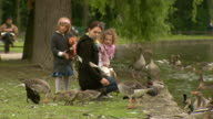 Englischer Garten, woman with her daughter feed the ducks, lake, water, lawn, trees