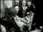 English people crowd police watching CU Crowd woman w/ British flag HA WS Bagpipe band marching on street MS King George VI saluting w/ Queen Lady...