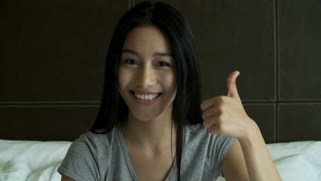 4K: Enthusiastic motivated attractive young woman giving a thumbs up gesture of approval and success with a beaming smile.