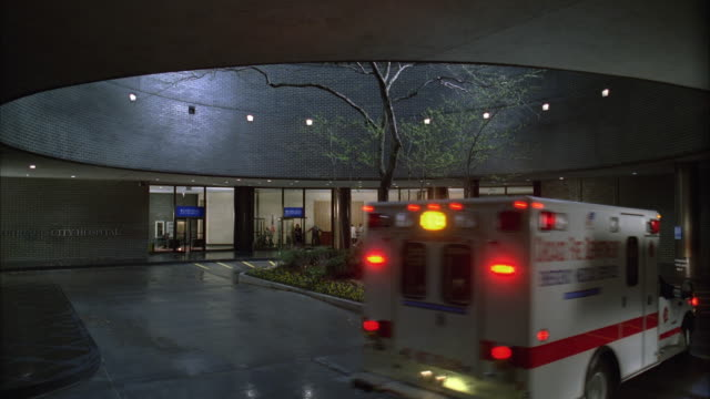 WS Entrance to modern hospital, ambulance arrives with flashing lights and doctors removing stretcher