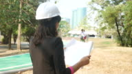 environment engineer using binocular and reading Plan Design Document