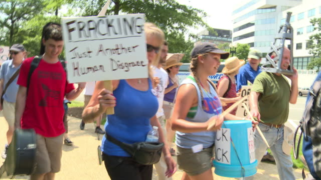 Environmentalists march chant and hold signs against fracking water pollution and FERC