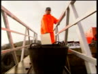 Oil slick CF TAPE NO LONGER AVAILABLE SPAIN Noia EXT RAINING WINDY LMSs Fishermen and fisherwomen working on beach in driving rain and wind PAN GV...