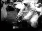 Epidemic prevention workers bring specimens of suspected contaminated objects from germ bomb drops to a scientist for examination