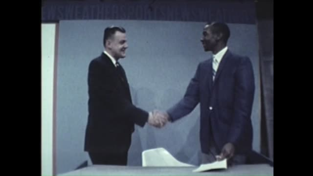 Ernie Banks at the WGNTV studio talking with journalists Banks reads the news at an anchor desk and shakes hands with anchor in 1969
