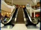 Escalators carrying people flank flight of stairs in shopping mall Michigan