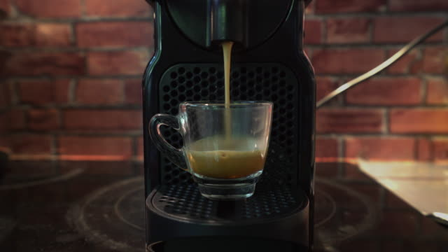 Espresso dripping form automated coffee maker into a cup