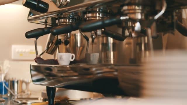 Espressomachine koffie in de beker gieten
