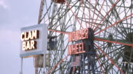 Establishing shot of a ferris wheel in Coney Island, Brooklyn at dusk - 4k
