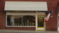 Establishing shot of a small town store front business called 'Bill's Doors & Hardware' featuring a brick exterior, awning and Texas flag waving in the breeze.