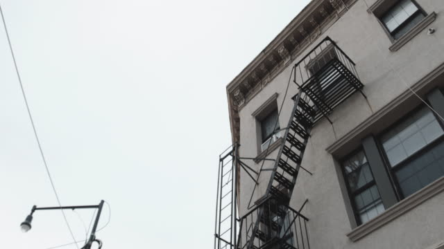 establishing shot of an unrecognizable fire escape and residential building - 4k
