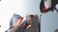 Establishing shot of flags flying in front of New York City's Rockefelelr Center.