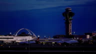 Establishing shot of the Control Tower and Theme Building, Los Angeles International Airport, with a Virgin America Airbus A320 taxiing past, Late Evening.