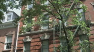 MS Establishing shot - Windows of Greenwich Village brick apartment building with architectural detail and tree branches / New York, New York, USA