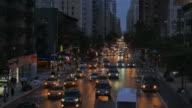 establishment shot of rush hour traffic commuting through city streets at night. metropolis cityscape view background