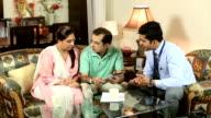 Estate agent explaining to a family on digital tablet, Delhi, India