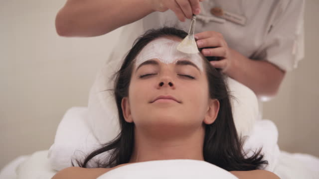 TU Esthetician applying mask to client during spa facial treatment / Stowe, Vermont, United States