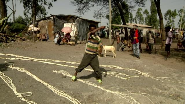 Ethiopan Boy cracks whip at camel market on August 05 2011 in Bati Ethiopia