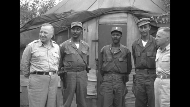 VS Ethiopian and American military personnel outside temporary structure / Communist North Korean officers arriving / large group of Americans...