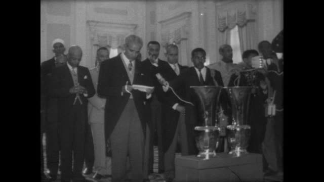 CU Ethiopian Emperor Haile Selassie in room full of officials and press / diplomats and admirers present or send gifts / children of Armed Forces...