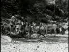 Ethiopian people moving through villages along trails in mountains crossing rivers on horseback crossing plains wading river walking w/ rifles...