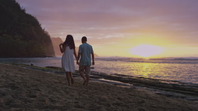 Ethnic couple walking up tropical beach