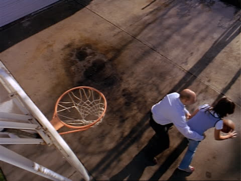 ethnic father in dressy work clothes plays basketball in driveway with his daughter