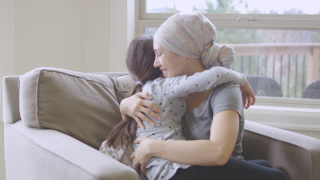 Ethnic young adult female with cancer hugging her daughter
