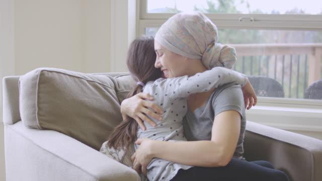 Etniska unga vuxna kvinnliga med cancer kramar hennes dotter