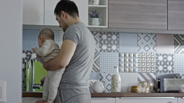 Eurasian man with baby boy cooking in kitchen