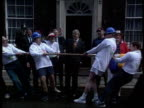 Conservative party ENGLAND London Downing St John Major MP stannds on doorstep watching tugofWar in progress PAN LR MS TugofWar in progress PAN LR as...