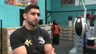 Boxer Amir Khan organises aid convoy for Syrian refugees ENGLAND Lancashire Bolton INT Men at boxing gym loading crates of bottled water British...