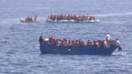 Thousands continue to cross Mediterranean Sea in dangerous conditions MEDITERRANEAN SEA Various shots migrants wearing orange life jackets as on...
