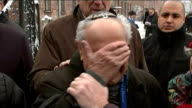 Stories of Holocaust survivors POLAND Auschwitz Group of people gathered at 'Arbeit Macht Frei' entrance gates/ Mordechai Ronen hugging man and...