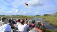 Everglades City Florida airboat ride fast with tourists riding on water wetlands of Everglades at Miccosukee Indian reserve