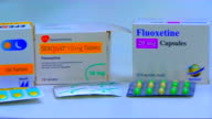 Packets of antidepressants including Efexor Seroxat Fluoxetine Prozac Blister pack of antidepressants hand taking pack of Fluoxetine from shelf then B