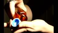 Hand tipping drugs capsules from bottle Drugs tipped from bottle onto surface