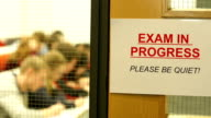 Exam in progress sign with Students behind