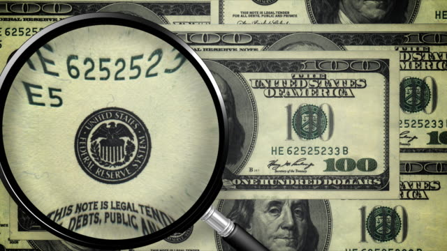 Examining the dollar bill with a magnifying glass, president winks